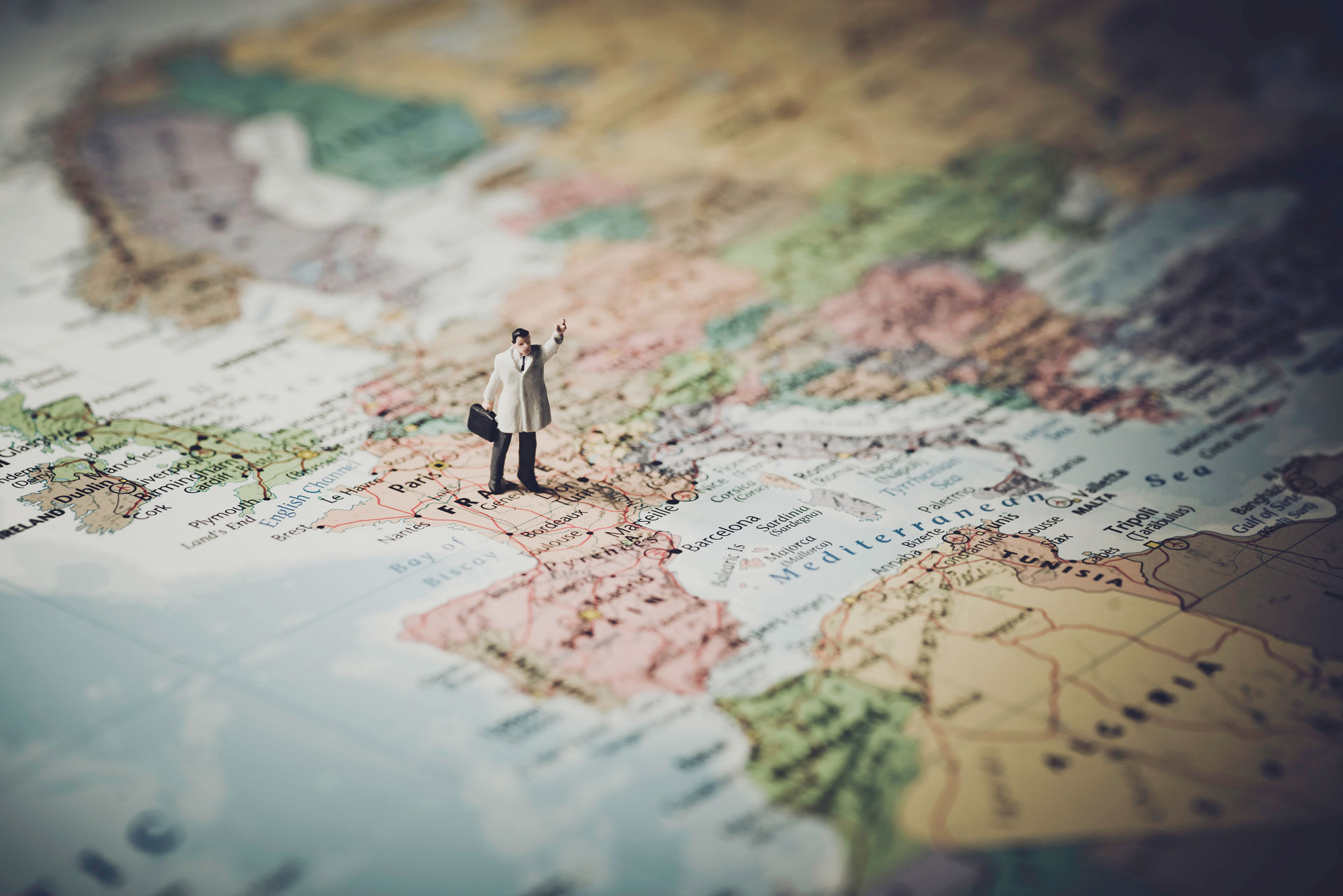 Muñeco parado en un mapa - CFGS Online Guía, Información y Asistencias Turísticas